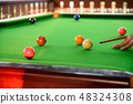 Man's hand playing snooker in bar with ball 48324308