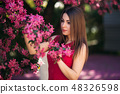 Beautiful lady stand by the big blooming tree voilet color. Happy girl with makeup in spring 48326598