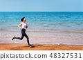 Woman running on the beach on a sunny day 48327531