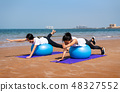 Women exercising with pilates ball on the beach 48327552