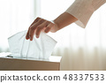 women hand picking napkin paper from tissue box 48337533