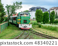The train rides a narrow path and carries tourists 48340221