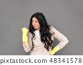 Freestyle. Mature lady in rubber gloves standing isolated on grey hand on hips showing fist 48341578