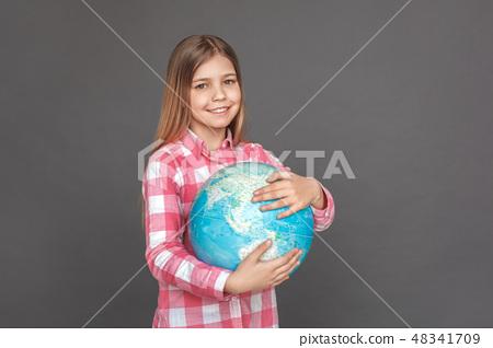 Freestyle. Girl standing isolated on grey hugging globe smiling joyful 48341709