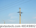 A pole with electric wires against a blue sky 48349802