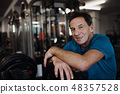 A senior man resting after workout exercise in gym. Copy space. 48357528