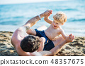A father with a toddler son playing on sand beach on summer holiday. 48357675