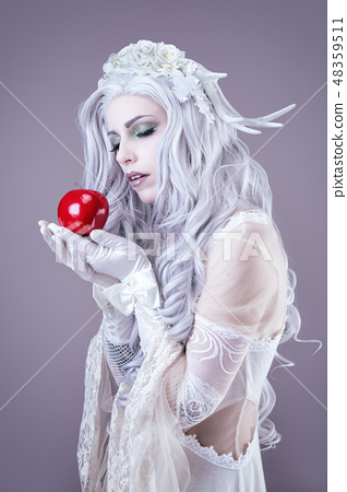 Young princess holding an apple in her hand 48359511