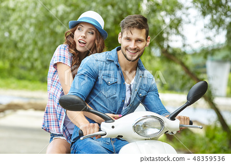 Riding with fun. Beautiful young couple riding scooter together 48359536