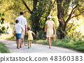 A rear view of family with small children walking barefoot on a road in summer. 48360383