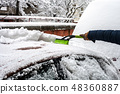 Young man cleaning his car from snow with brush 48360887