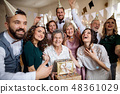 A portrait of multigeneration family with presents on a indoor birthday party. 48361029