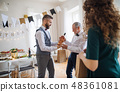 A man giving a bottle of wine to his father on indoor birthday party, a celebration concept. 48361081