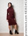 Beautiful woman posing near white brick wall 48363453