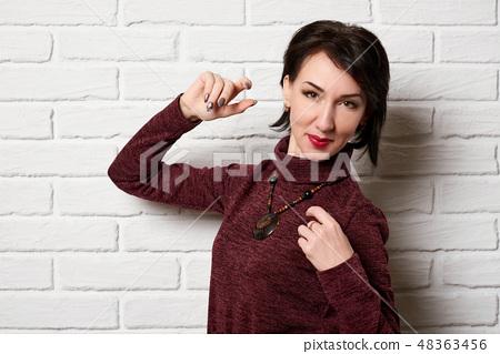 Beautiful woman posing near white brick wall 48363456