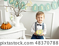Cute boy in a white shirt and a tassel butterfly sits at a table in a white room on a table Easter 48370788
