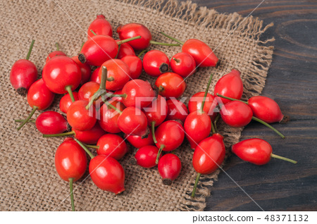 fresh rose hips on a wooden table with sacking 48371132