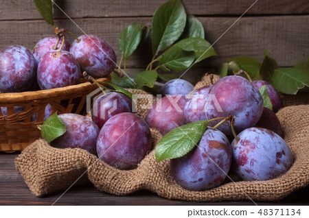 plum in a wicker basket on the wooden background with sackcloth 48371134