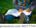 Little child writing on a notebook in the park. 48377744