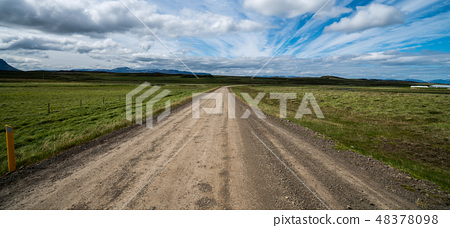 Empty dirt road through countryside landscape. 48378098