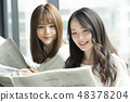 Two women reading a newspaper on the window side 48378204