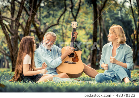 Happy family play guitar and sing together in park 48378322
