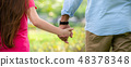 Father and daughter holding hands in the park. 48378348