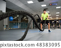 Man with battle ropes exercise in the fitness gym. 48383095