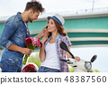 Portrait of romantic man giving flowers to woman 48387560