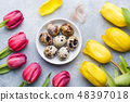 Bright flowers tulips and quail eggs on stone back 48397018