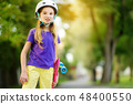 Pretty little girl learning to skateboard  48400550
