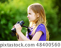 Funny little girl looking through binoculars on sunny summer day 48400560