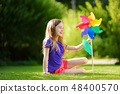 Adorable little girl holding colorful toy pinwheel on sunny summer day 48400570