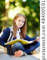 Adorable little schoolgirl studying outdoors 48400591