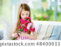 Adorable smiling little girl holding flowers for her mom on mother's day 48400633
