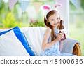 Cute little girl wearing bunny ears eating chocolate Easter rabbit 48400636