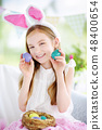 Cute little girl wearing bunny ears playing egg hunt on Easter 48400654
