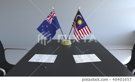 Flags of New Zealand and Malaysia and papers on the table. Negotiations and signing an international 48401657