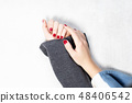 Closeup of hands of a young woman with dark red manicure on nails against white background 48406542