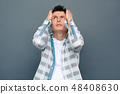 Man isolated on gray wall free style standing looking up holding head thoughtful 48408630