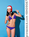 New Year Celebration. Woman in bikini and santa hat standing isolated on blue wall with glass of 48409087