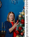 Very beautiful girl stands near the Christmas tree 48410904