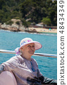 Senior woman enjoys summer vacation in a sea voyage on a pleasure boat. 48434349