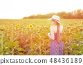 Long-haired girl in a hat and dress stands 48436189