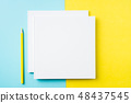two white square notebook on yellow and blue paper 48437545