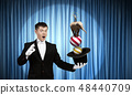 Man magician with cylinder hat 48440709