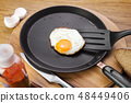 Fried eggs on a pan 48449406