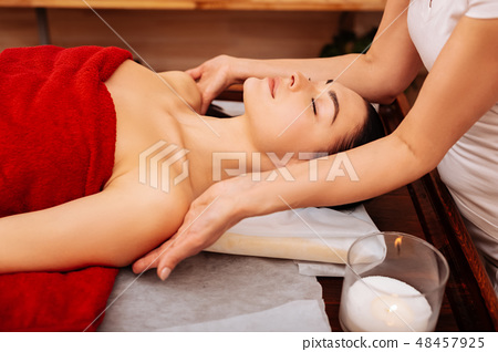 Diligent professional masseuse touching shoulders of her client 48457925