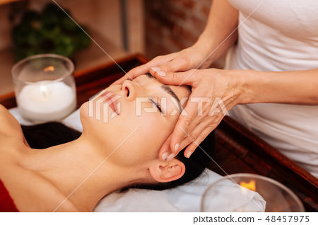 Experienced masseuse in white t-shirt making relaxing massage for face 48457975