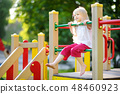 Cute little girl having fun on a playground outdoors in summer. 48460923